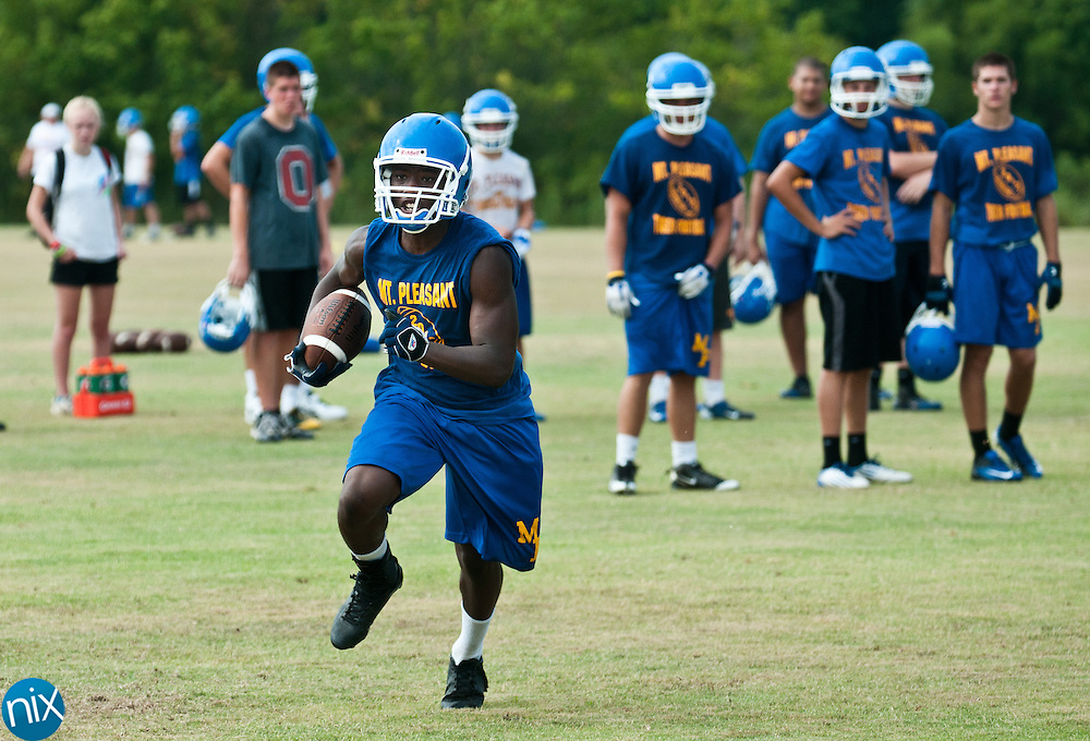 Mount Pleasant's Denzel Gilmore carries the ball while running through plays at football practice Tuesday, July 31  at Mount Pleasant High School. (photo by James Nix)
