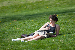 © Licensed to London News Pictures. 20/04/2015. Bristol, Avon, UK. A woman on her phone enjoying the sunny weather in Bristol today, 20th April 2015. The South West of England is set for more warm temperatures and plenty of sunshine this week. Photo credit : Rob Arnold/LNP