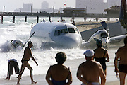 A cargo plane rests in the surf along North Miami Beach, in Florida, as tourists and sunbathers go about their daily routine, December, 7, 2001. The Miami-based Trans Air cargo plane crash landed after the pilot reported problems with the twin engine plane. Both the pilot and co-pilot walked away from the crash with minor injuries. The National Transportation Safety Board is investigating the cause of the crash.  PHOTO BY:COLIN BRALEY