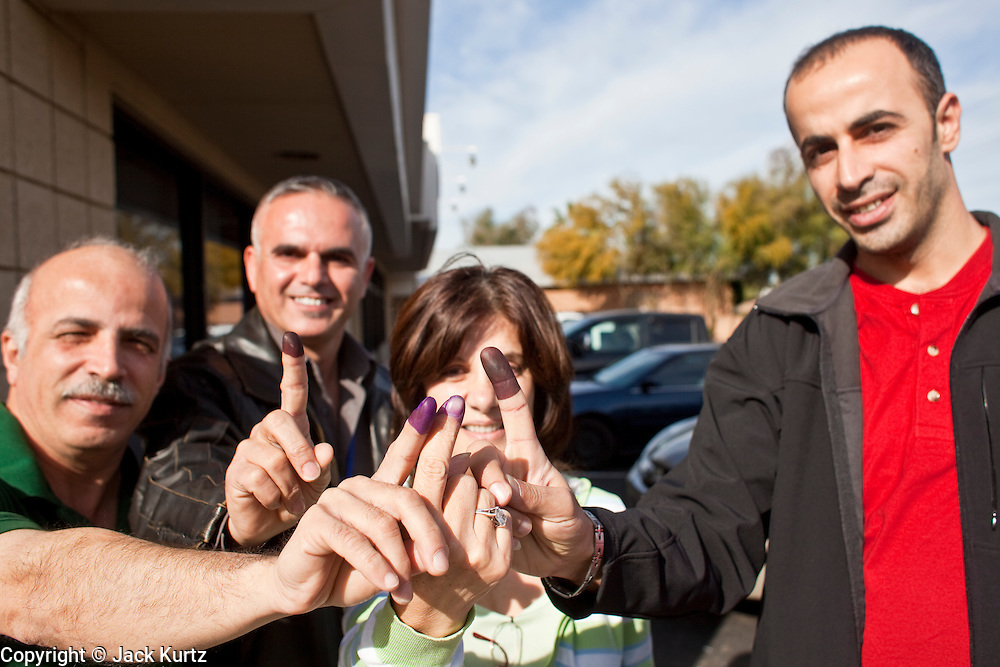 Mar. 6, 2010 -- PHOENIX, AZ: Iraqi voters show off their purple stained fingers after voting in their national election at the Iraqi polling place in Phoenix, AZ, Saturday, March 6. Phoenix is one eight cities in the United States where Iraqi citizens can vote in their national parliamentary elections. Voting started Friday and will end Sunday. Election workers said they expected between 4,000 and 6,000 people would vote at the Phoenix polling place.   Photo by Jack Kurtz
