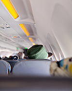 Rastafarian hat wearer sitting a few rows ahead of the camera on a plane. WATERMARKS WILL NOT APPEAR ON PRINTS OR LICENSED IMAGES.