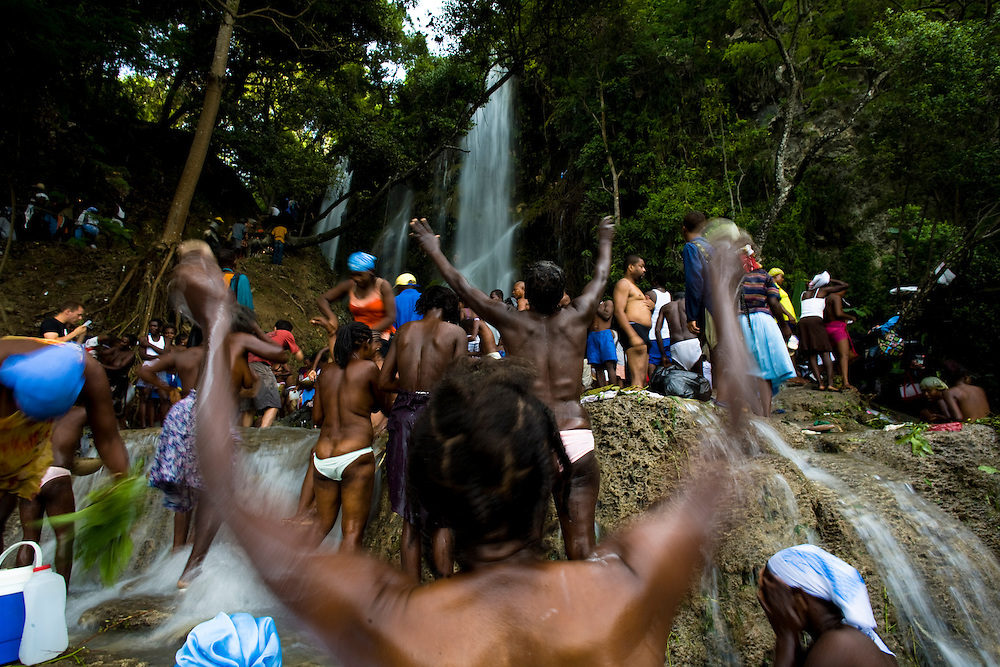 Haitian pilgrims gather at the waterfall at Saut d'Eau on July 16th, the anniversary of the 1983 sighting of the Virgin Mary, alternately identified as the Vodou loa, or spirit, of Erzulie Freda, the Goddess of Love..The waterfall at Saut D'Eau is the site of the largest Vodou and Catholic pilgrimage in Haiti. A second sighting of the Virgin was reported during the American occupation. Each year, thousands of Haitian pilgrims make their way to Saut D'Eau to bathe in the sacred water and revel in the presence of the loa, particularly Erzulie and Damballah the Serpent, father of all life and keeper of spiritual wisdom, who is said to live in the falls. The water is believed to be curative and many women come to Saut d'Eau seeking fertility.