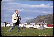 Boy carries puffin chick he rescued in Heimaey park for release at shore;August/Westmann Islands Iceland