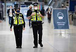 © Licensed to London News Pictures. 15/06/2020. London, UK. British Transport Police wear face masks as they patrol the concourse at Waterloo Station. New rules allowing some non-essential retail businneses to open and mandatory face masks on public transport have started today. Photo credit: Peter Macdiarmid/LNP