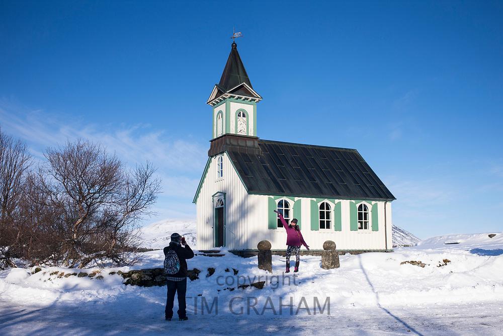 Tourist couple taking photograph at famous church chapel Pingvallakirkja in Thingvellir National Park - Pingvellir -  in Iceland