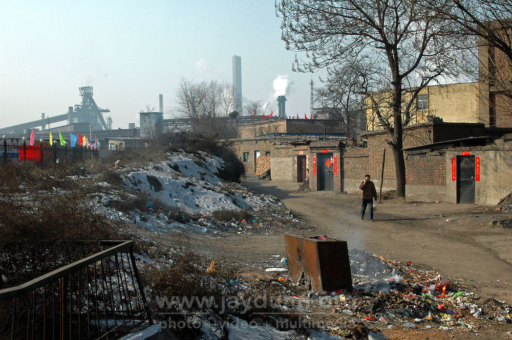 "China, Taiyuan, 2008. A factory worker leaves his home next to ""Tai Gang,"" Taiyuan Iron and Steel, Shanxi's largest employer and a vital part of China's metal production capacity.."