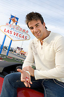 Man holding dice, Las Vegas 'welcome' sign in background