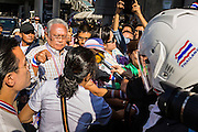"15 JANUARY 2014 - BANGKOK, THAILAND: SUTHEP THAUGSUBAN, former Deputy Prime Minister of Thailand and leader of the Shutdown Bangkok anti-government protests, arrives at the protest site in the Asoke intersection. Tens of thousands of Thai anti-government protestors continued to block the streets of Bangkok Wednesday to shut down the Thai capitol. The protest, ""Shutdown Bangkok,"" is expected to last at least a week. Shutdown Bangkok is organized by People's Democratic Reform Committee (PRDC). It's a continuation of protests that started in early November. There have been shootings almost every night at different protests sites around Bangkok. The malls in Bangkok are still open but many other businesses are closed and mass transit is swamped with both protestors and people who had to use mass transit because the roads were blocked.    PHOTO BY JACK KURTZ"