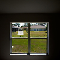 TAMPA, FL -- March 22, 2011 -- Homes are seen through the window of vacant home in North Port, Fla., 2011.  A recent study showed that one and five homes in the state of Florida is vacant.