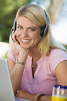 Woman Using Laptop Wearing Telephone Headset