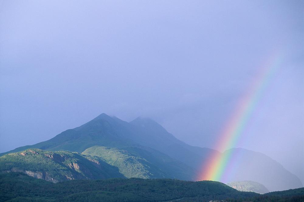 USA, Alaska, Rainbow and clearing summer storm over Chugach Range mountains near Matanuska Glacier