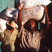 Haitians laborers carry bags of rice shipped from Miami at a warehouse in Port au Prince.