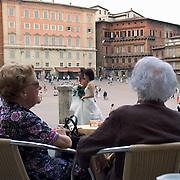 Two women at cafe table on the Piazza Del Campo sit in front row seats watching the world pass before them, Siena, Italy<br />