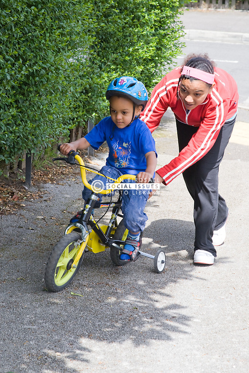 Teenaged girl helping her younger brother learn to ride a bike,