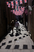 Couple walk below British Union Jack flags strung together across a London alleyway, near Bond Street.