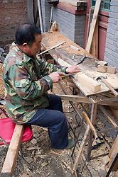 Craftsman working on renovation of old house in traditional courtyard in a Beijing hutong or lane in China