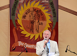 © Licensed to London News Pictures.  16/07/2017; Tolpuddle, Dorset, UK. JEREMY CORBYN, Leader of the Labour Party, speaks from the main stage at the Tolpuddle Trade Union Festival. Frances O' Grady, TUC General Secretary was also in attendance. Tolpuddle has been a place of great importance to the Labour Movement from the moment news broke of the harsh sentences imposed on the six farm workers who led the formation of the union in 1834. In 1834, farm workers in west Dorset formed a trade union. Unions were lawful and growing fast but six leaders of the union were arrested and sentenced to seven years' transportation for taking an oath of secrecy. Protests swept across the country. Thousands of people marched through London and many more organised petitions and protest meetings to demand their freedom. The Tolpuddle Martyrs Museum tells the story of the Martyrs arrest, trial and punishment, leading to the foundation of modern day trade unionism. Every year in July, thousands of people attend the Tolpuddle Martyrs' Festival for a weekend of family entertainment, stalls, political debate, comedy, music and a grand procession of trade unions with banners through the village. Picture credit : Simon Chapman/LNP