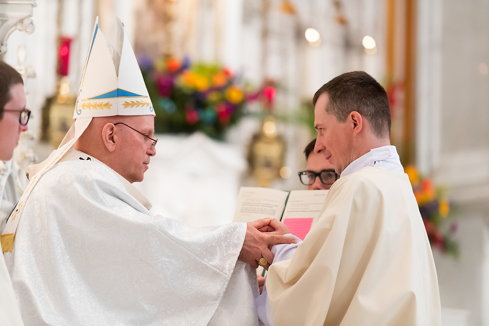 DENVER, CO - MAY 13: Denver Archbishop Samuel Aquila holds Bogusław Rębacz's hands for the promise of respect and obedience for his ordination of the priesthood at the Cathedral Basilica of the Immaculate Conception on May 13, 2017, in Denver, Colorado. (Photo by Daniel Petty/for Denver Catholic)