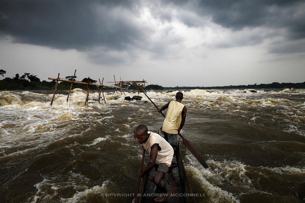 Fishermen make their way to a series of fishing posts in the middle of the Congo river at the last cataract of Boyoma Falls, near Kisangani, DR Congo. The Boyoma Falls, known as Wagenia Falls by the local tribe of the same name, consists of seven cataracts spread over 100km with the river dropping 60 meters and finishing at Kisangani. The explorer H.M. Stanley in 1877 described this last cataract, of the then Stanley Falls, as a 'tumultuous rush'. The fishing here is some of the most difficult as fishermen must battle the full force of the flow, and it is here that the Lualaba River becomes the Congo river.