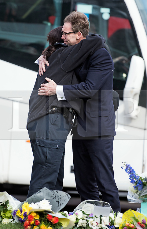 © Licensed to London News Pictures. 22/03/2018. London, UK. TOBIAS ELLWOOD MP hugs a police officer as he looks at flowers left on Parliament Square, outside the Houses of Parliament in Westminster, London on the one year anniversary of the the Westminster Bridge Terror attack. A lone terrorist killed 5 people and injured several more, in an attack using a car and a knife. The attacker, 52-year-old Briton Khalid Masood, managed to gain entry to the grounds of the Houses of Parliament and killed police officer Keith Palmer. Photo credit: Ben Cawthra/LNP