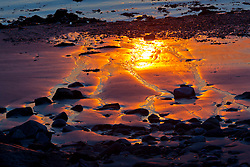 Sunrise reflections on the beach at Great Island Common in New Castle, New Hampshire.