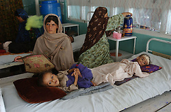 KABUL,AFGHANISTAN - AUGUST 29: Afghan women sit by their children Tofan, 1, left, and Zeeya-u-din, 1, who suffer from severe malnutrition in the Indira Ghandi Hospital for Children August 29, 2002 in Kabul Afghanistan. The hospital has 300 beds but usually it is filled at double capacity with only 118 doctors. One in four children die before the age of 5 in Afghanistan. (Photo by Ami Vitale/Getty Images)