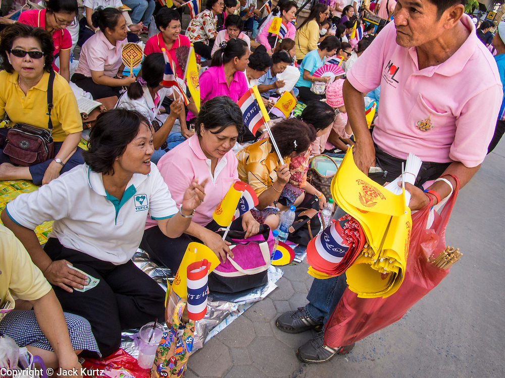 01 AUGUST 2013 - BANGKOK, THAILAND: A woman buys the yellow flag of the Thai monarchy in front of Siriraj Hospital, before Bhumibol Adulyadej, the King of Thailand, left the hospital Thursday. The King, 85, was discharged from Bangkok's Siriraj Hospital, where he has lived since September 2009. He traveled to his residence in the seaside town of Hua Hin, about two hours drive south of Bangkok, with his wife, 80-year-old Queen Sirikit, who has also been treated in the hospital for a year.      PHOTO BY JACK KURTZ