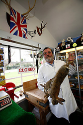 UK ENGLAND BERKSHIRE CHAPEL ROW 22MAR11 - Butcher Martin Fidler (60) poses for a portait with two rabbits at his butchers' shop in Chapel Row, Berkshire, England. Mr Fidler and his wife are long-standing friends of the Middleton family and have received an invite to the Royal Wedding on the 29th of April 2011...jre/Photo by Jiri Rezac..© Jiri Rezac 2011