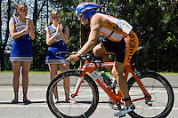 JEROME A. POLLOS/Press..Toby Radcliffe, from Carshalton, Surrey, Great Britain., is cheered on by Coeur d'Alene High School cheerleaders Kiela Boruvka, left, and Carrie Baldwin during the 112-mile bike ride Sunday at the Ford Ironman Coeur d'Alene.