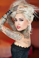 Portrait of tattooed young woman wearing corset with hands in hair