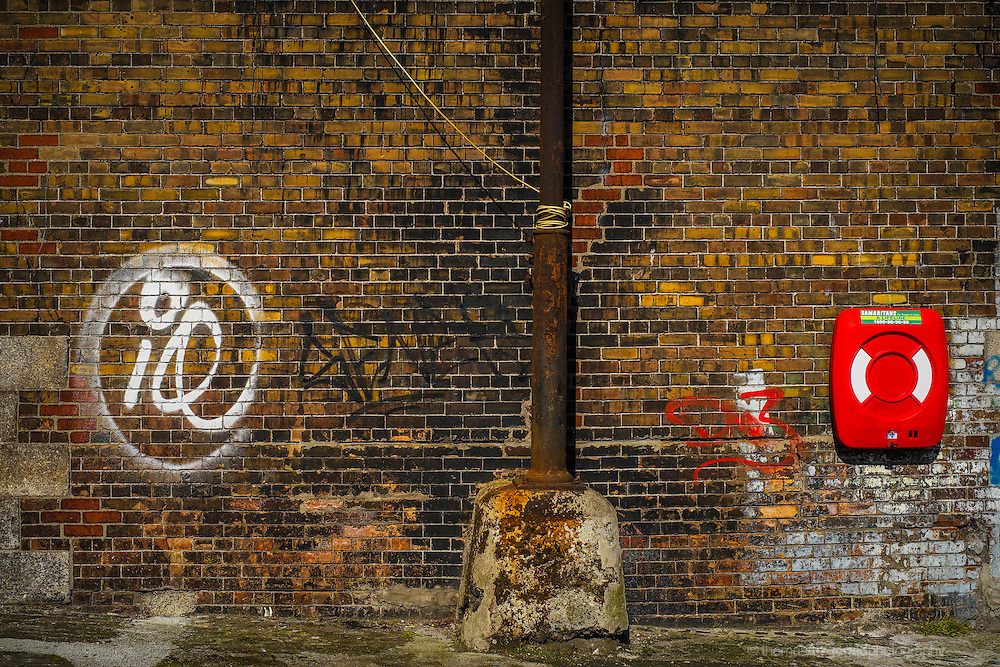A richly textured red brick wall on the quays of Dublin City is covered in graffiti and peeling paint