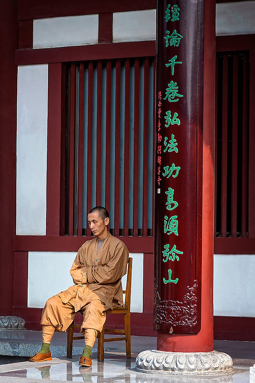 A Buddhist monk sitting on a chair in front of the temple.