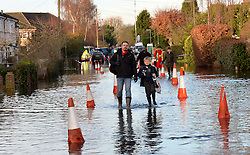 A father talks his son to school in Staines, Surrey as flood waters rise, United Kingdom, Thursday 13th February 2014. Picture by David Dyson / i-Images