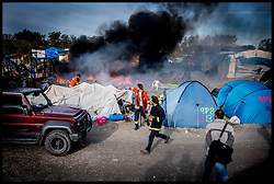 October 27, 2016 - Calais, Northern France, France - Volunteer firefighters put of fires in the  middle of the burning tent in  the migrant camp as refugees start to leave the Calais Jungle migrant camp the day after it caught fire and the French police closed it down.(Credit Image: © Andrew Parsons/i-Images via ZUMA Wire)