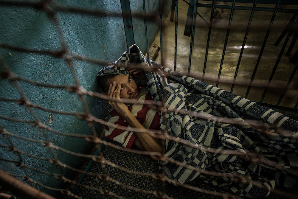 BARQUISIMETO, VENEZUELA - JULY 28, 2016: Nearly everyday, Ismael Pacheco, a patient diagnosed with paranoid psychosis, drags his mattress into a storage room full of broken beds, where he prefers to take naps, usually covering his head with his blanket or hands, and often accompanied by one of the stray dogs that roam in and out of the hospital. He has a proper bed, but the nursing staff let him sleep there during the day because it is where he prefers to be. The economic crisis that has left Venezuela with little hard currency has also severely affected its public health system, crippling hospitals like El Pampero Psychiatric Hospital by leaving it without the resources it needs to take care of patients living there, the majority of whom have been abandoned by their families and rely completely on the state to meet their basic needs. PHOTO: Meridith Kohut