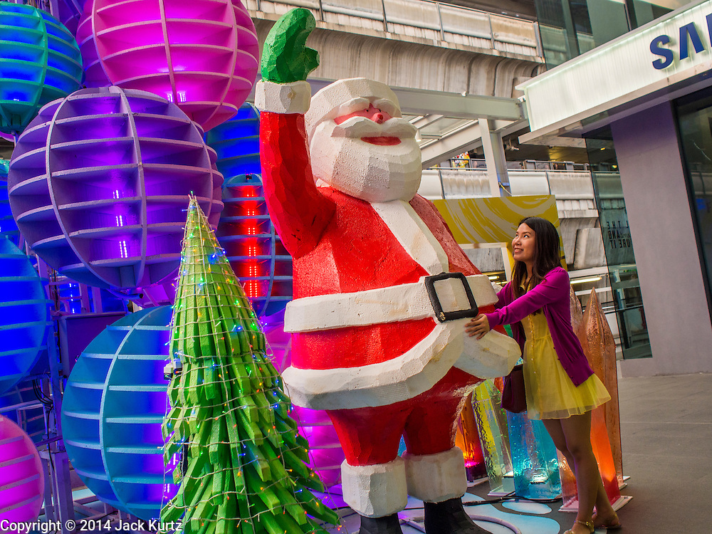 10 DECEMBER 2014 - BANGKOK, THAILAND: A woman looks at a statue of Santa Claus in Siam Square, a shopping mall in Bangkok's Ratchaprasong District. Thailand is overwhelmingly Buddhist. Christmas is not a legal holiday in Thailand, but Christmas has become an important commercial holiday in Thailand, especially in Bangkok and communities with a large expatriate population.         PHOTO BY JACK KURTZ