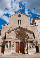 Facade of a beautiful, medieval stone church against a blue sky in Arles, France.
