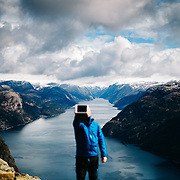 A man uses his mobile device to take a selfie with a view of Lysefjord from Preikestolen (Pulpit Rock) in Norway
