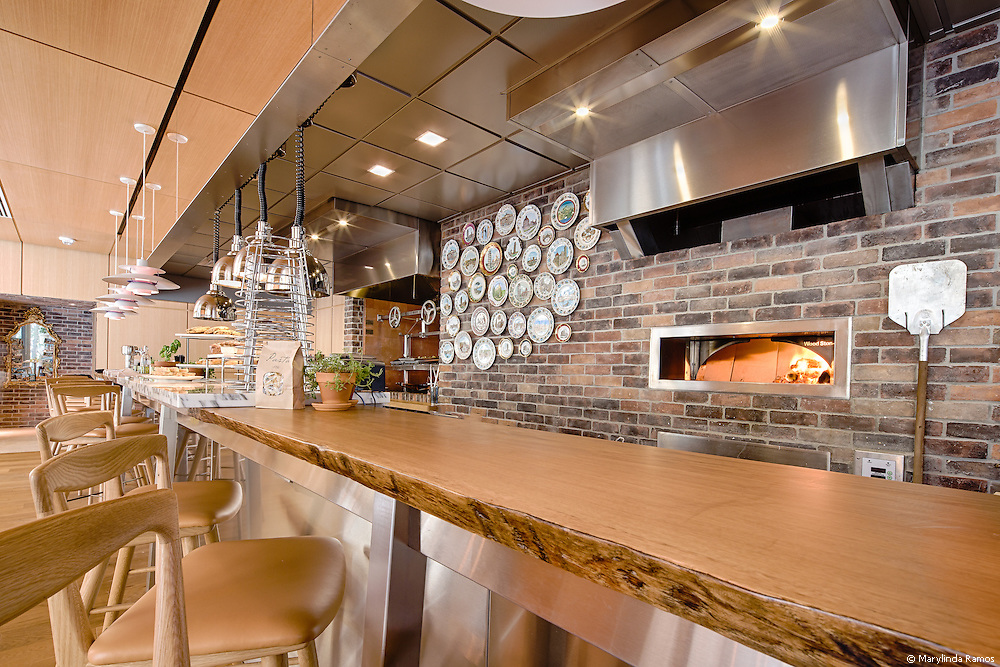 The wood-fired oven at Fi'lia by Michael Schwartz complements the natural tones of the decor - wood countertops and chairs; potted herbs on counters and walls, and abundant natural light.