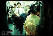 Woman in kimono leans on door windown as she travels on subway in Tokyo. Japan