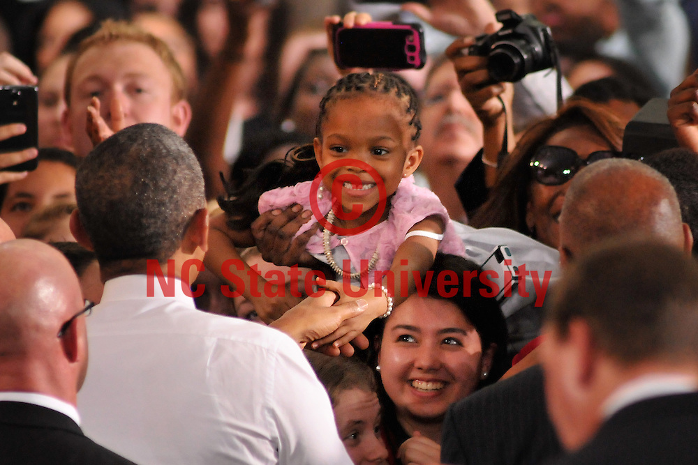 President Barack Obama shakes the hand of little girl after his speech.