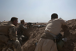 20/10/2016. Bashiqa, Iraq. Peshmerga fighters look towards the burning town of Tiskharab, where Kurdish colleagues are clearing out Islamic State positions during an operation to retake the ISIS held town of Bashiqa Iraq, today (20/10/2016).<br /> <br /> Launched in the early hours of today with support from coalition special forces and air strikes, the attack is part of the larger operation to retake Mosul from the Islamic State, and involves both the Kurds and the Iraqi Army. The city of Bashiqa, around 9 miles north of Mosul, is one of several gateway areas that must be taken before any attempted offensive on Mosul itself.<br /> <br /> Despite the peshmerga suffering several casualties after militants fought back using mortars, heavy machine guns and snipers, the Kurdish forces were quickly taking ground with Haider al-Abadi, the Iraqi prime minister, stating that the operation to retake Mosul was progressing faster than expected. Photo credit: Matt Cetti-Roberts/LNP