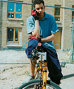 Teenager on his bike, talking into a mobile phone outside some new housing, 1990's