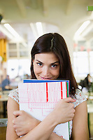 Portrait of happy young businesswoman with books in office