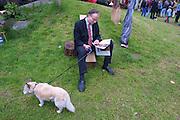 Am Rand einer Freiluftveranstaltung im Wendland sitzt ein Mann mit seinem Hund auf einer Wiese und liest eine Zeitschrift.