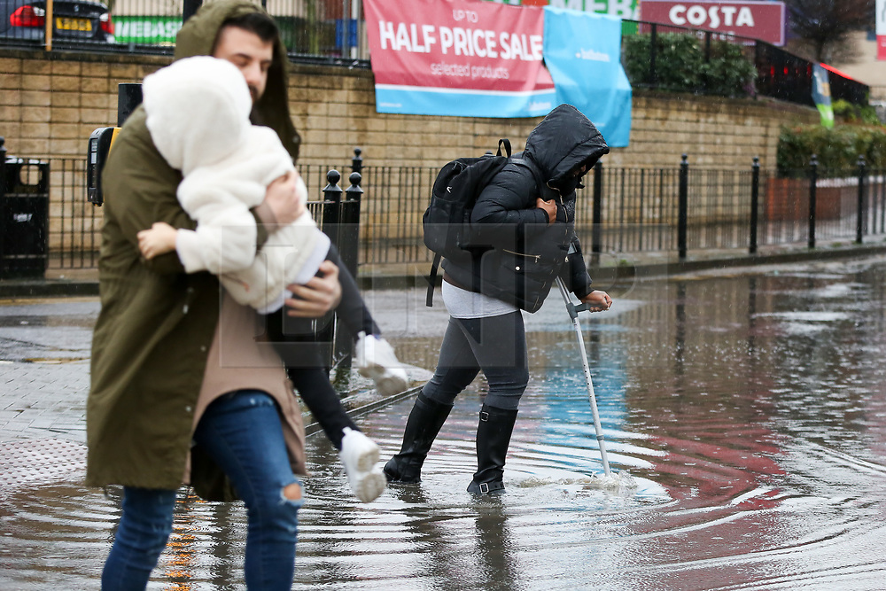 © Licensed to London News Pictures. 15/01/2020. London, UK. A member of public holds a child and a woman with a crutch walk through a flood on Green Lanes in north London following heavy overnight rainfall. Photo credit: Dinendra Haria/LNP
