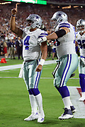 Dallas Cowboys quarterback Dak Prescott (4) points skyward and celebrates with Dallas Cowboys offensive guard Zack Martin (70) after running for a second quarter touchdown that ties the score at 7-7during the 2017 NFL week 3 regular season football game against the against the Arizona Cardinals, Monday, Sept. 25, 2017 in Glendale, Ariz. (©Paul Anthony Spinelli)