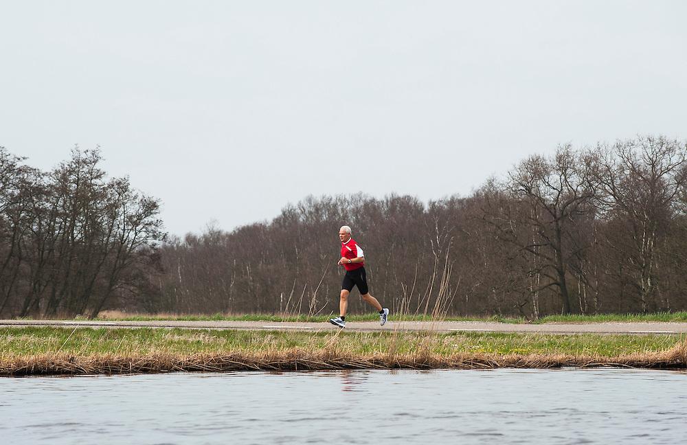 Nederland, Zaanstad, 17  april 2013.Hardloper langs het Noordzeekanaal..Foto(c): Michiel Wijnbergh