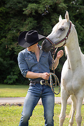 cowboy enjoying time with a horse outdoors