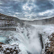 Gullfoss is a waterfall located in the canyon of Hv&iacute;t&aacute; River in southwest Iceland. It&rsquo;s one of the most popular tourist attractions in the country. The wide Hv&iacute;t&aacute; rushes southward and about a kilometre above the falls it flows down into a wide curved staircase and then abruptly plunges into the deep crevice you can see in this image. <br />